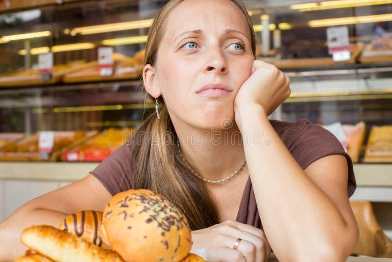 Jolie jeune femme mangeant des bonbons dans le café Mauvaises habitudes santé images stock