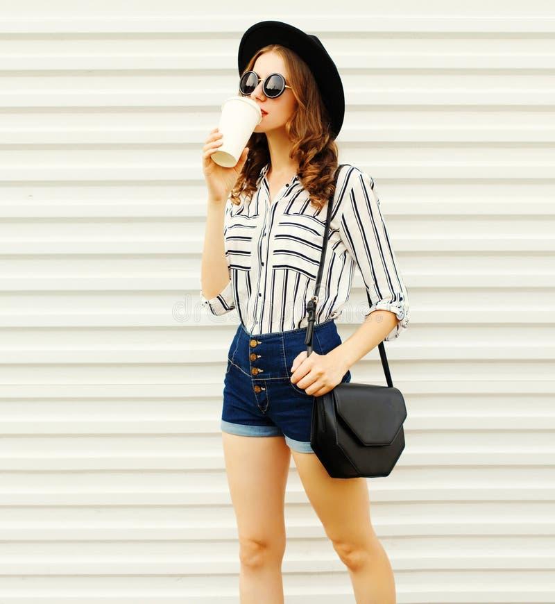 Jolie jeune femme marchant avec la tasse de café dans le chapeau rond noir, shorts, chemise rayée blanche sur le mur blanc photo libre de droits