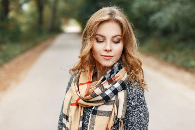 Jolie jeune femme mignonne européenne avec les cheveux blonds dans un manteau élégant gris avec une écharpe beige à carreaux de c images stock