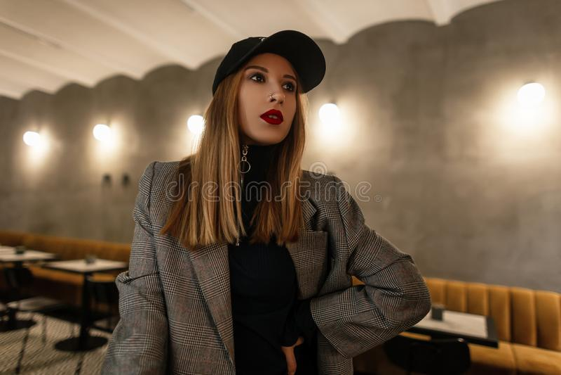 Jolie jeune femme modèle dans une veste à carreaux à la mode dans le rétro style dans un chapeau noir à la mode avec un nez percé photos libres de droits