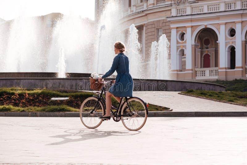 Jolie jeune femme montant un vélo près de la fontaine photos stock