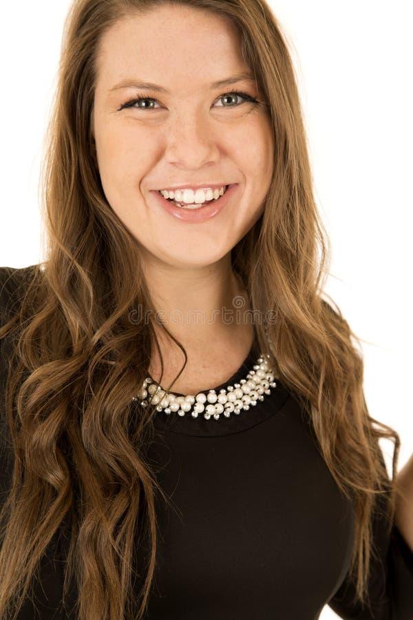 Jolie jeune femme portant une robe noire avec des perles photo stock