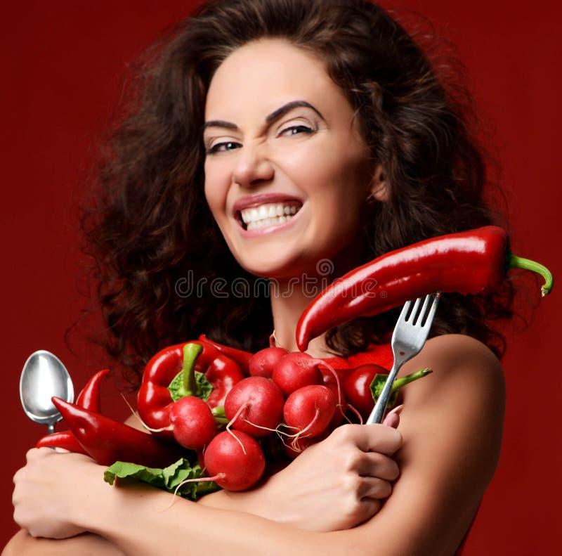Jolie jeune femme posant avec le sourire rouge frais de persil de laitue de feuilles de vert de poivre de piment de radis de légu images stock