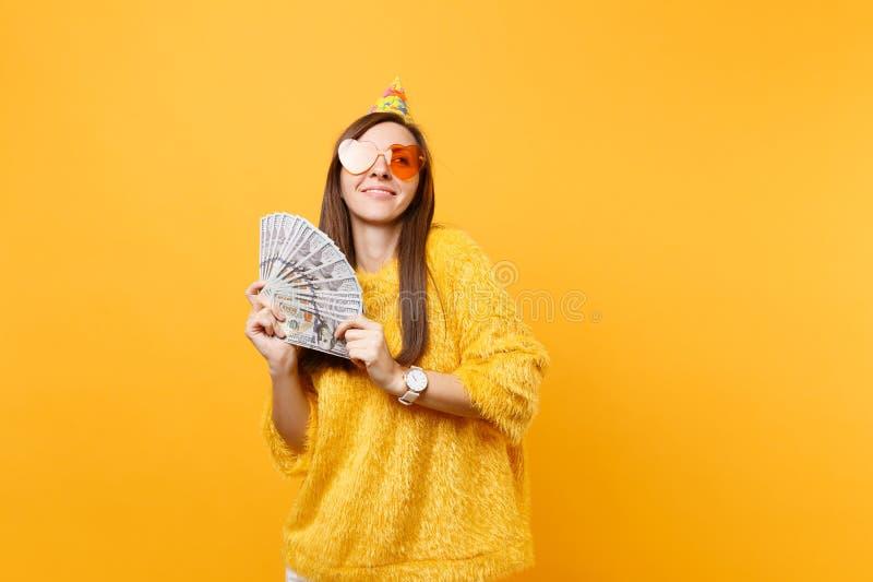 Jolie jeune femme rêveuse dans le chapeau orange de fête d'anniversaire en verre de coeur recherchant tenant un bon nombre de paq photos libres de droits