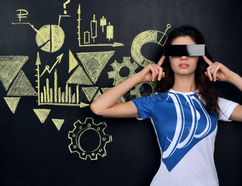 Jolie jeune femme regardant des graphiques et des symboles de marché boursier photos stock
