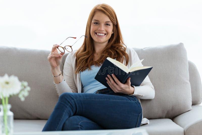 Jolie jeune femme regardant l'appareil-photo tout en lisant un livre sur le sofa à la maison photographie stock libre de droits