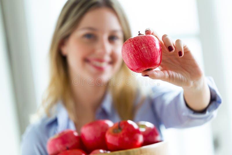 Jolie jeune femme regardant la caméra tout en montrant la pomme rouge à la maison image libre de droits