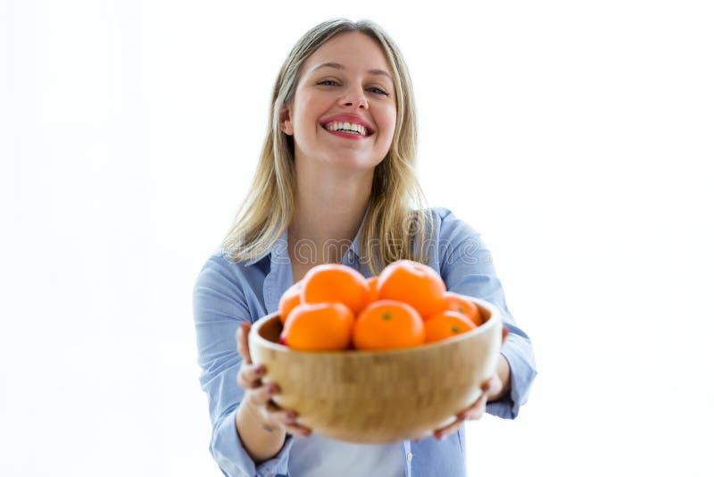 Jolie jeune femme regardant la caméra tout en tenant une cuvette avec des oranges au-dessus du fond blanc photographie stock libre de droits