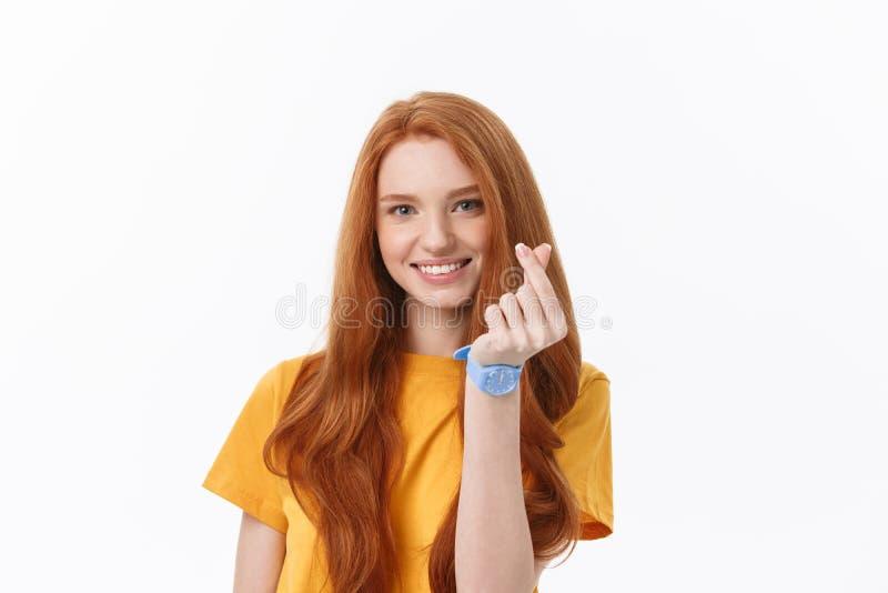 Jolie jeune femme rousse romantique faisant un geste de coeur avec un sourire tendre heureux images libres de droits