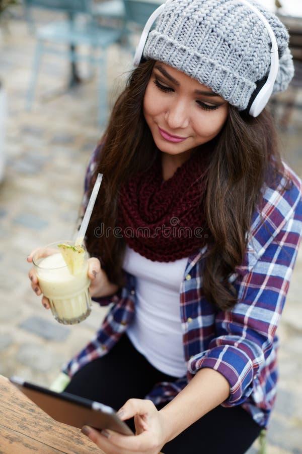 Jolie jeune femme s'asseyant dans la terrasse et le  frais potable e d'été de restaurant de juiÑ images libres de droits