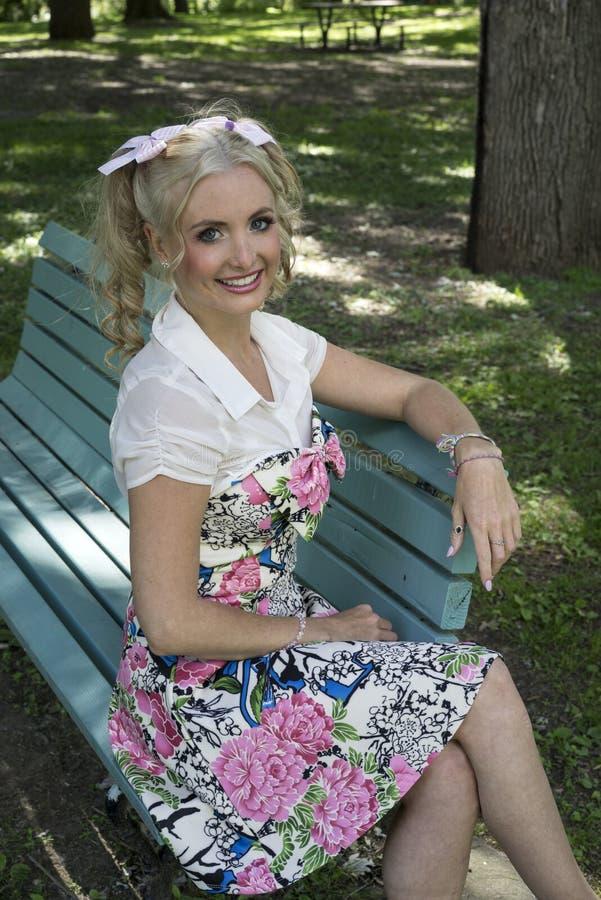 Jolie jeune femme s'asseyant sur un banc de parc photographie stock libre de droits