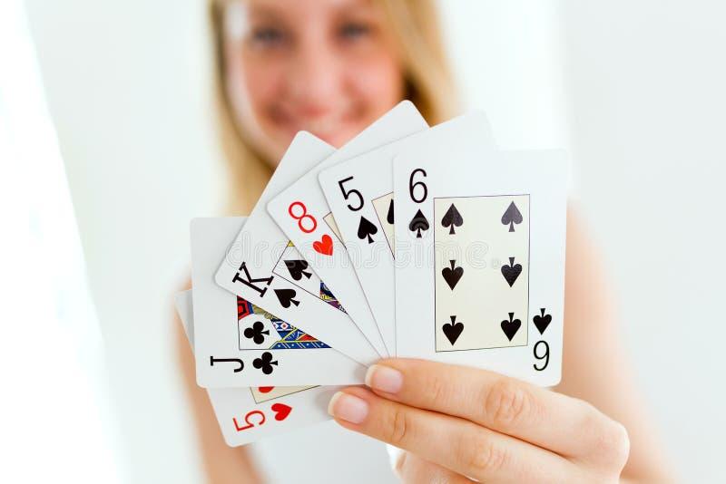 Jolie jeune femme souriant et tenant des cartes de tisonnier à la maison images libres de droits