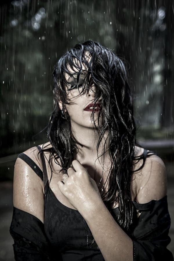 Jolie jeune femme sous la pluie d'automne en parc de palais photo libre de droits
