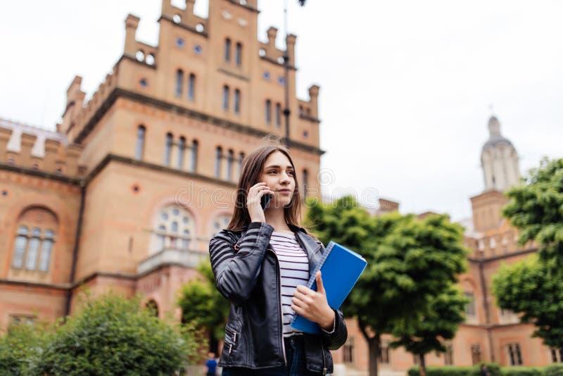 Jolie jeune femme sur le campus d'université parlant au téléphone photographie stock libre de droits