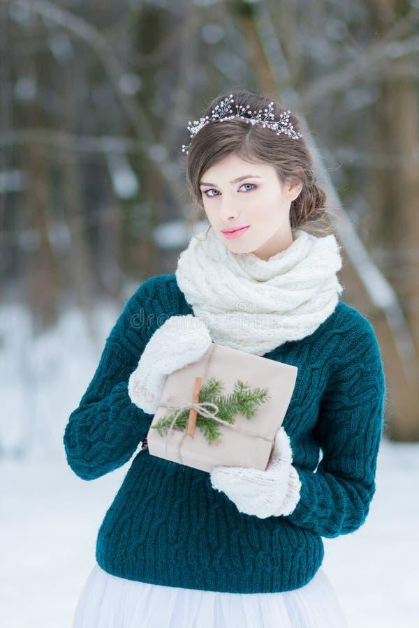Jolie jeune femme tenant le cadeau de Noël images stock