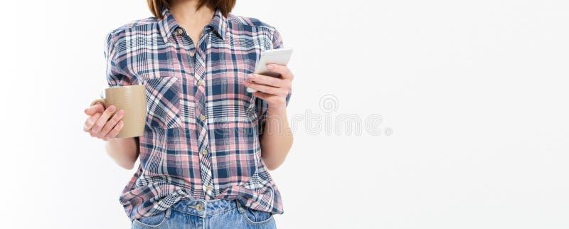 Jolie jeune femme tenant le t?l?phone intelligent, utilisant le dispositif, verres ?l?gants de port, sourire, tenant une tasse, d images stock