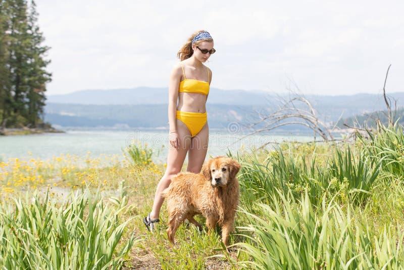 Jolie jeune fille marchant près d'un lac avec son chien image libre de droits