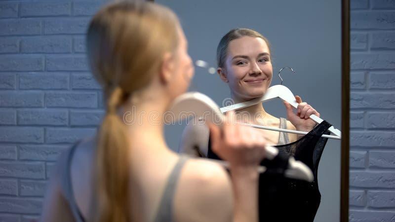 Jolie jeune pensée femelle au choix de robe regardant dans la préparation d'événement de miroir images libres de droits