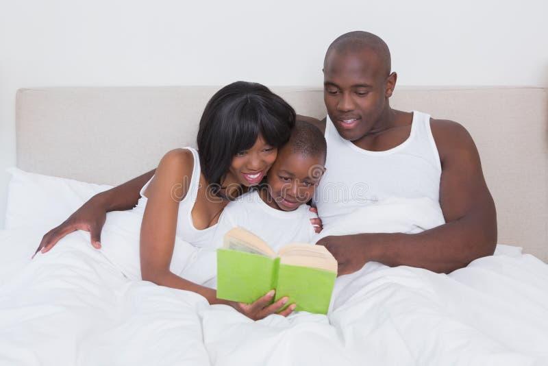 Download Jolie Lecture De Couples Avec Son Fils Dans Le Lit Ensemble Photo stock - Image du mâle, durée: 56485030