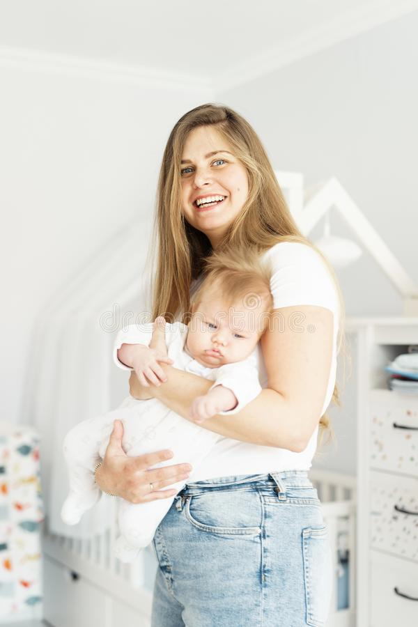 Jolie longue-heared maman blonde et fils nouveau-né dans des ses bras photo stock