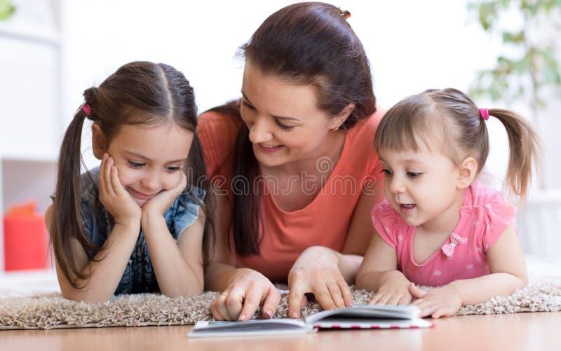 Jolie mère lisant un livre à ses filles image stock
