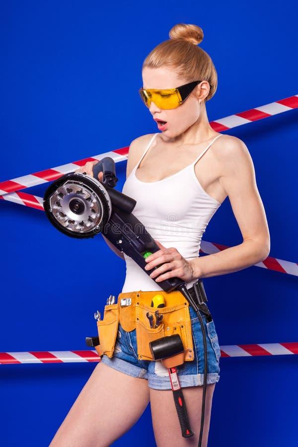 Jolie, mince fille de constructeur dans la chemise blanche, ceinture de constructeur, constructeur photo libre de droits