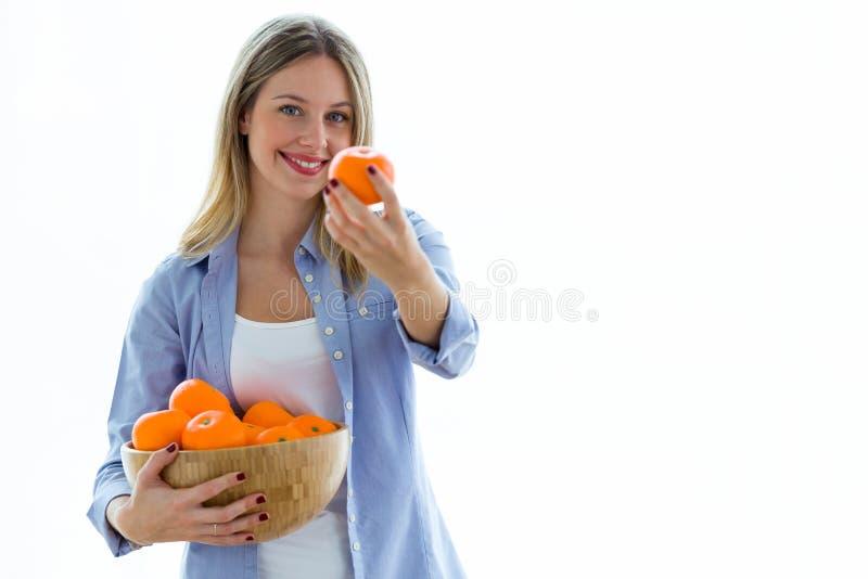 Jolie orange d'apparence de jeune femme à la caméra tout en tenant une cuvette au-dessus du fond blanc photos stock
