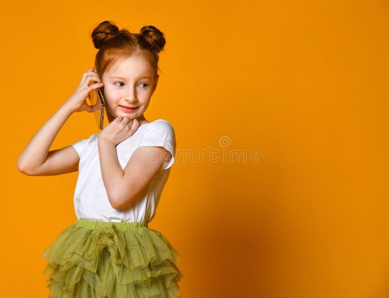 Jolie petite fille émotive parlant par le téléphone portable image stock