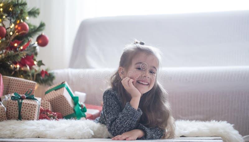 Jolie petite fille s'étendant sur le plancher dans sa chambre à la maison près de l'arbre de Noël photo libre de droits