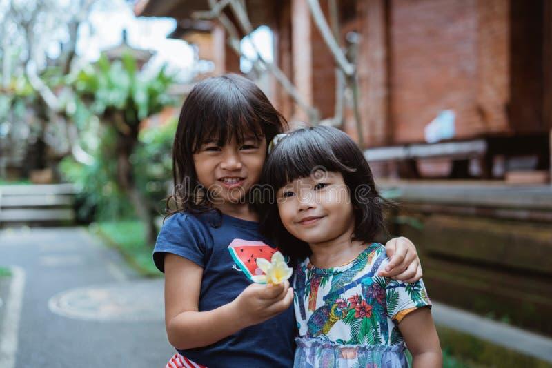 Jolie position de fille du bonheur deux devant la maison photos stock