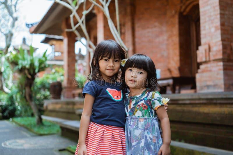 Jolie position de la fille deux devant la maison traditionnelle photographie stock libre de droits