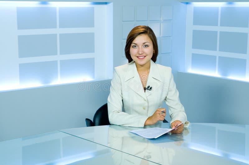 Jolie présentatrice au studio léger de TV photographie stock