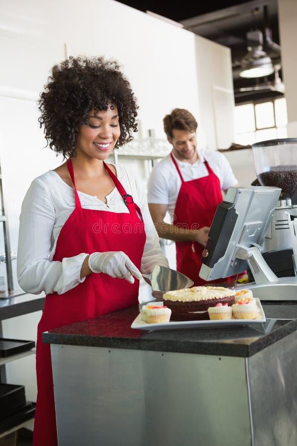 Jolie serveuse découpant le gâteau en tranches avec le serveur derrière elle image stock
