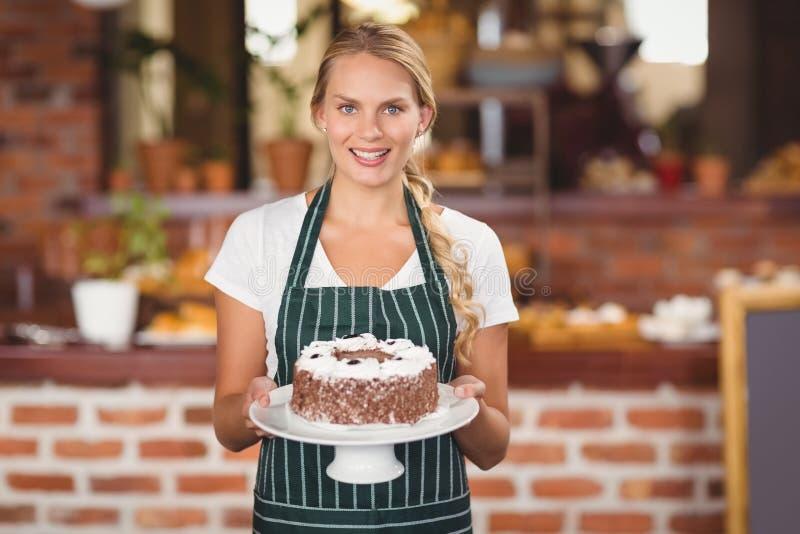 Jolie serveuse tenant un gâteau de chocolat images libres de droits