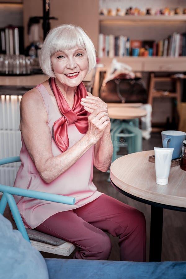 Jolie vieille dame aux cheveux courts frottant ses mains avec lisser la crème photos libres de droits
