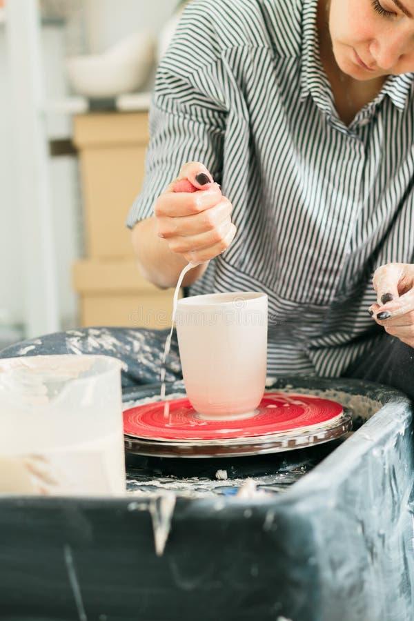Jolies femmes travaillant à la roue de potier dedans le studio photo stock