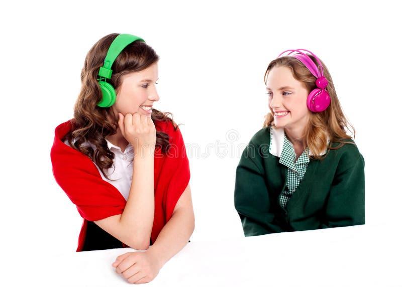 Jolies filles appréciant la musique. Regarder l'un l'autre photos libres de droits