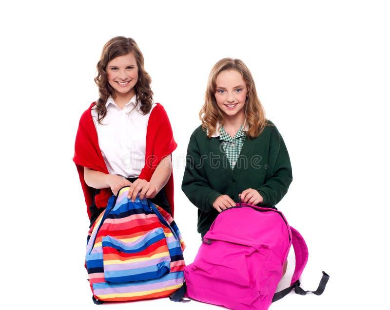 Jolies filles ouvrant le sac d'école photo libre de droits