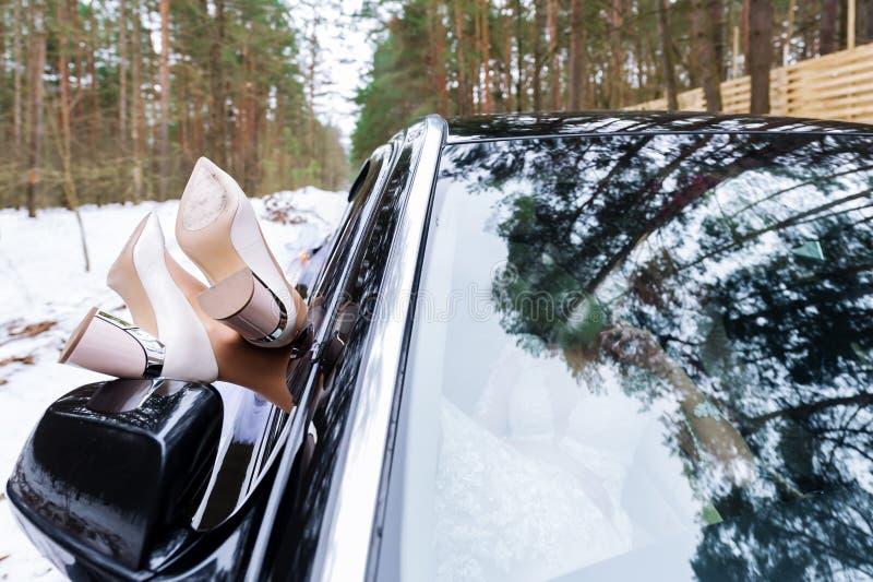 Jolies jambes de jeunes mariées dans des talons blancs hors de la fenêtre de voitures l'épousant photos libres de droits