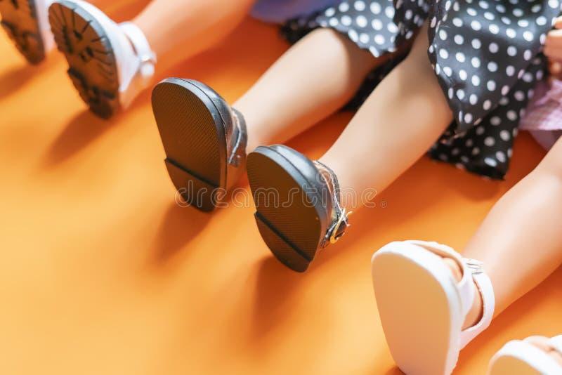 Jolies jambes de poupées de fille utilisant des sandales et des jupes s'étendant sur le fond orange b photographie stock