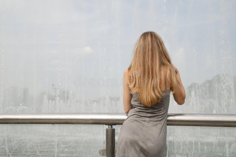 Jolies jeune femme et fontaine photographie stock libre de droits