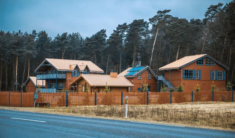 Jolies maisons en bois près de la route goudronnée images stock