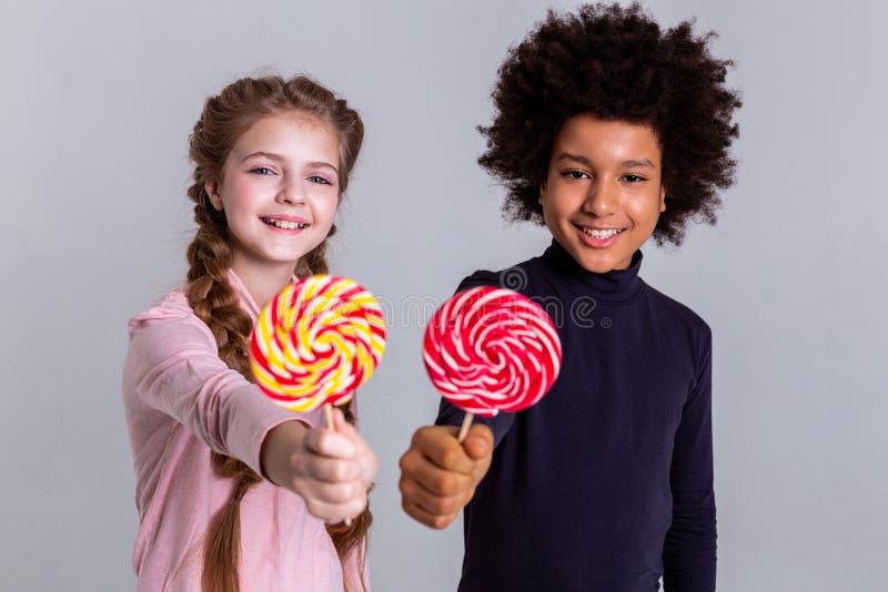 Jolis enfants beaux restant tout près et posant pour le photoshoot image stock