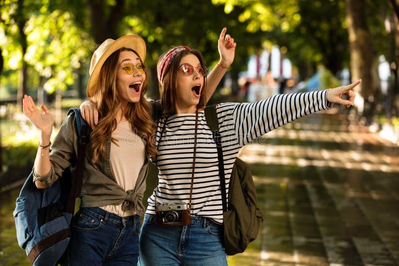 Jolis jeunes amis heureux de femmes marchant dehors avec des sacs à dos étreignant le pointage images libres de droits
