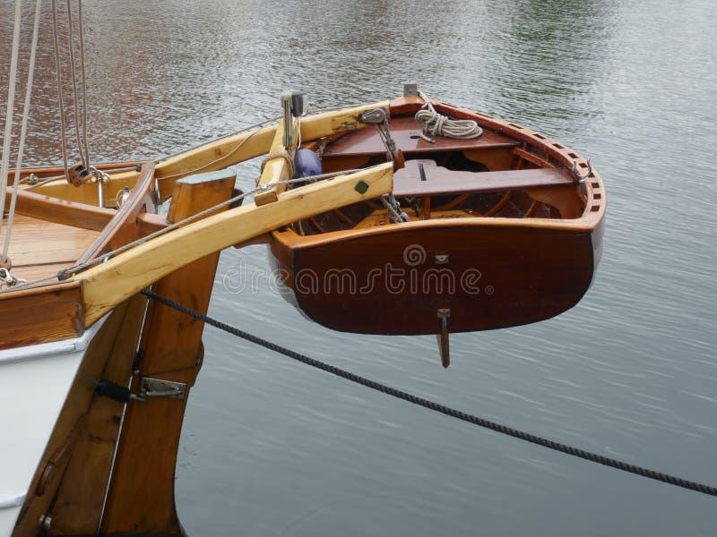Jolle liten eka som göras av mahognyträ, fäst till aktern av en segla yacht arkivfoto