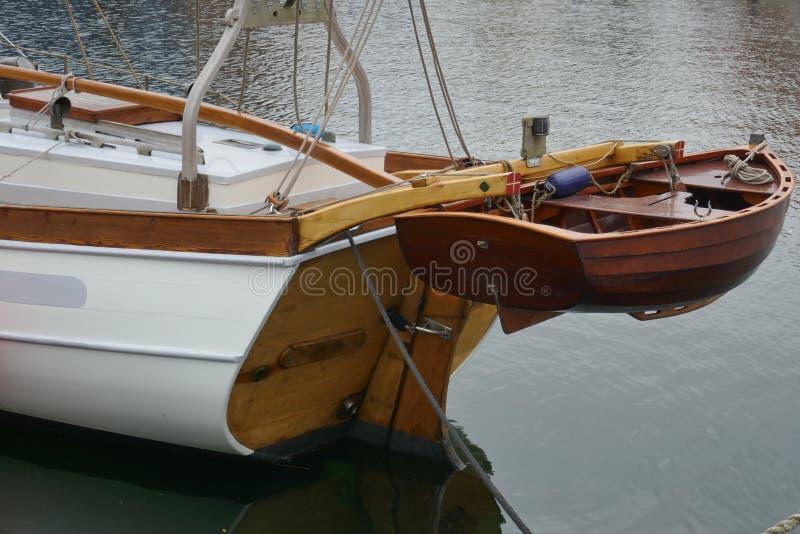 Jolle liten eka som göras av mahognyträ, fäst till aktern av en segla yacht royaltyfri fotografi