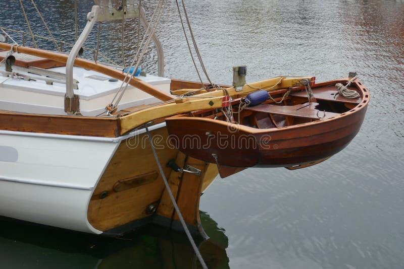Jolle liten eka som göras av mahognyträ, fäst till aktern av en segla yacht royaltyfri foto