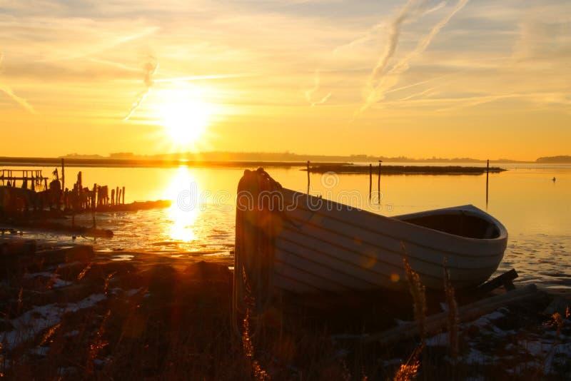 Jolle på kust i solnedgången arkivbild