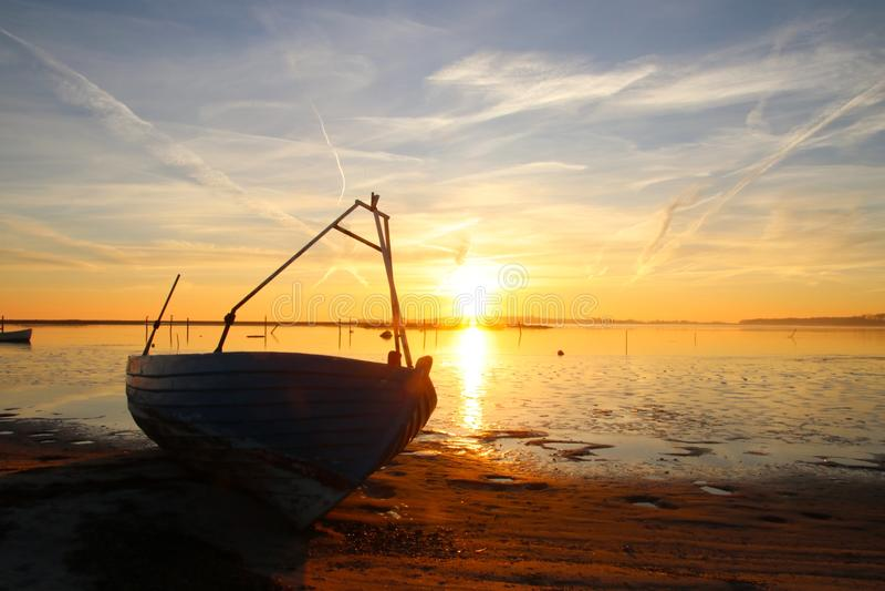 Jolle på stranden på solnedgången royaltyfri fotografi