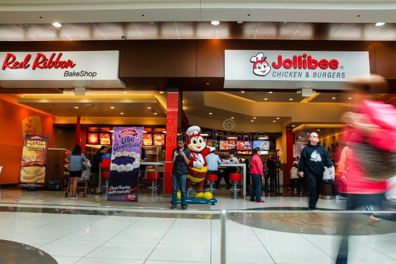 Jollibee restaurang och röd bandbakeshop med kunder royaltyfri fotografi